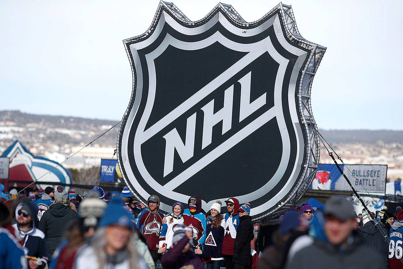 FILE - In this Saturday, Feb. 15, 2020, file photo, fans pose below the NHL league logo at a display outside Falcon Stadium before an NHL Stadium Series outdoor hockey game between the Los Angeles Kings and Colorado Avalanche, at Air Force Academy, Colo. (AP Photo/David Zalubowski, File)