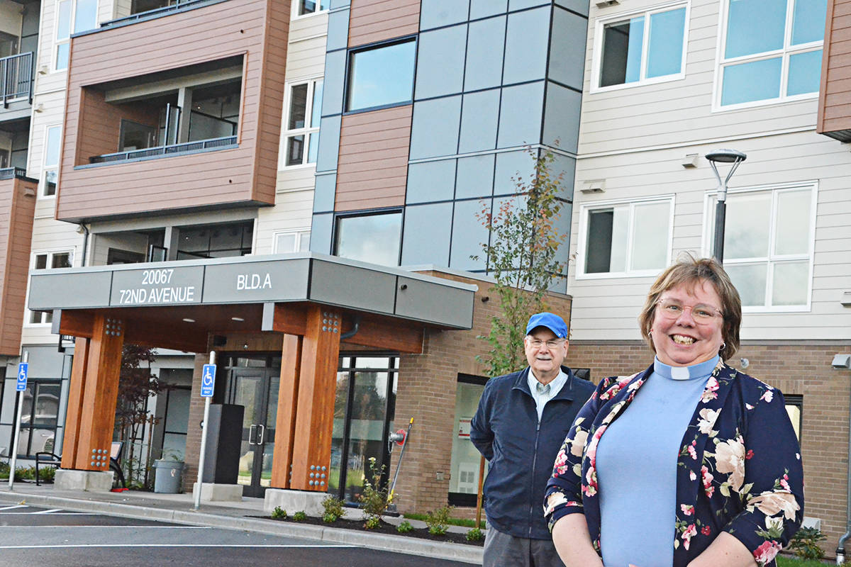 Pastor Kristen Steele and Steve Trummler of Shepherd of the Valley Lutheran Church in front of the new four-storey seniors housing building that sits on church land. (Matthew Claxton/Langley Advance Times)
