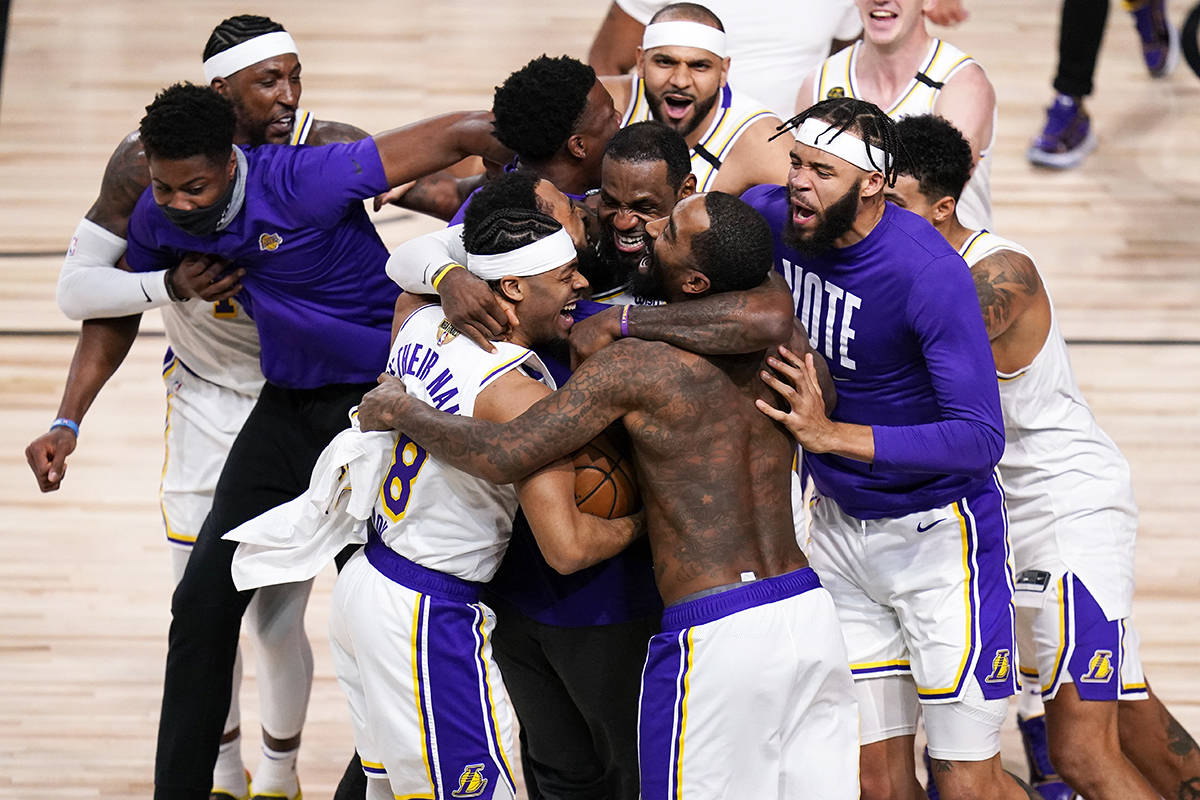 The Los Angeles Lakers players celebrate after the Lakers defeated the Miami Heat 106-93 in Game 6 of basketball's NBA Finals Sunday, Oct. 11, 2020, in Lake Buena Vista, Fla. (AP Photo/John Raoux)