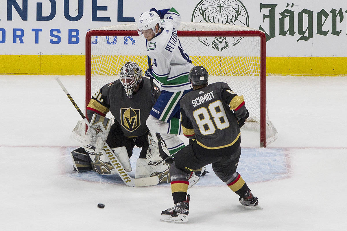 Vegas Golden Knights' goalie Robin Lehner (90) makes the save as Vancouver Canucks' Elias Pettersson (40) jumps and Nate Schmidt (88) defends during first period NHL Western Conference Stanley Cup playoff action in Edmonton on Tuesday, Aug. 25, 2020. THE CANADIAN PRESS/Jason Franson