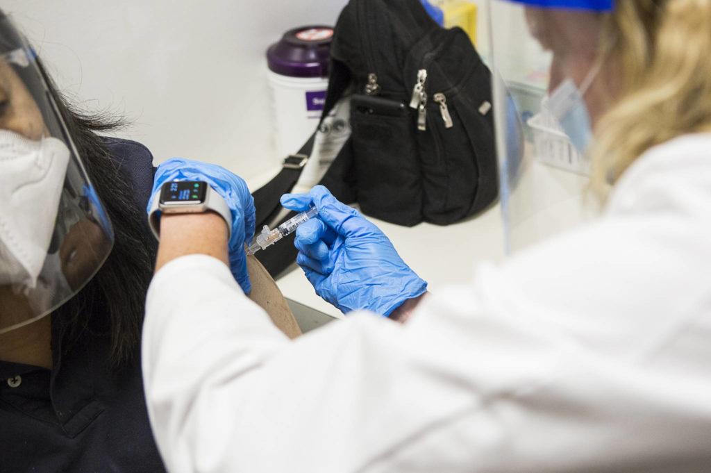 QFC Pharmacist Becky Buerhaus administers a flu shot on Wednesday, Sept. 9, 2020 in Everett, Wa. (Olivia Vanni / The Herald)