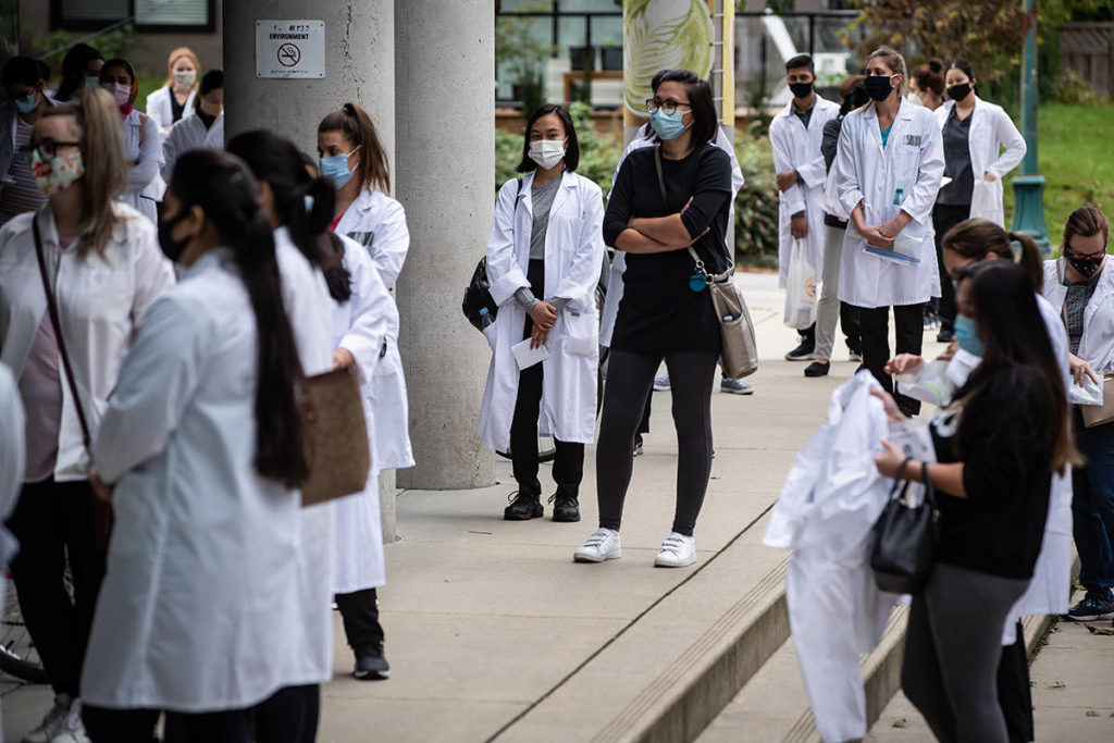 FILE – People wear face masks and stand apart from one another to curb the spread of COVID-19 as they wait in line to take a pharmacy technician exam at Vancouver Community College, in Vancouver, B.C., Sunday, Sept. 20, 2020. THE CANADIAN PRESS/Darryl Dyck