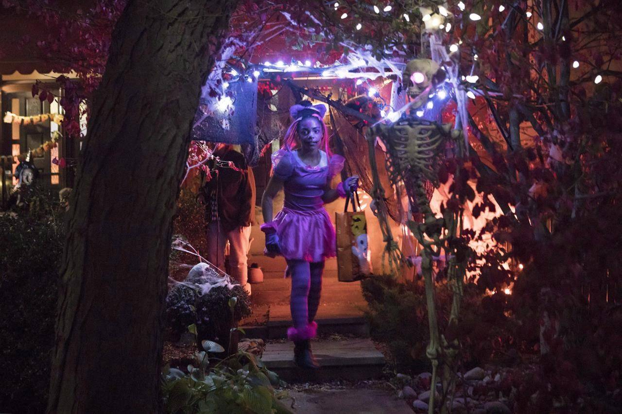 Eleven-year-old Hayley McDermott walks down the pathway of a decorated house during Halloween celebrations in Toronto, Tuesday, Oct. 31, 2017. THE CANADIAN PRESS/Chris Young