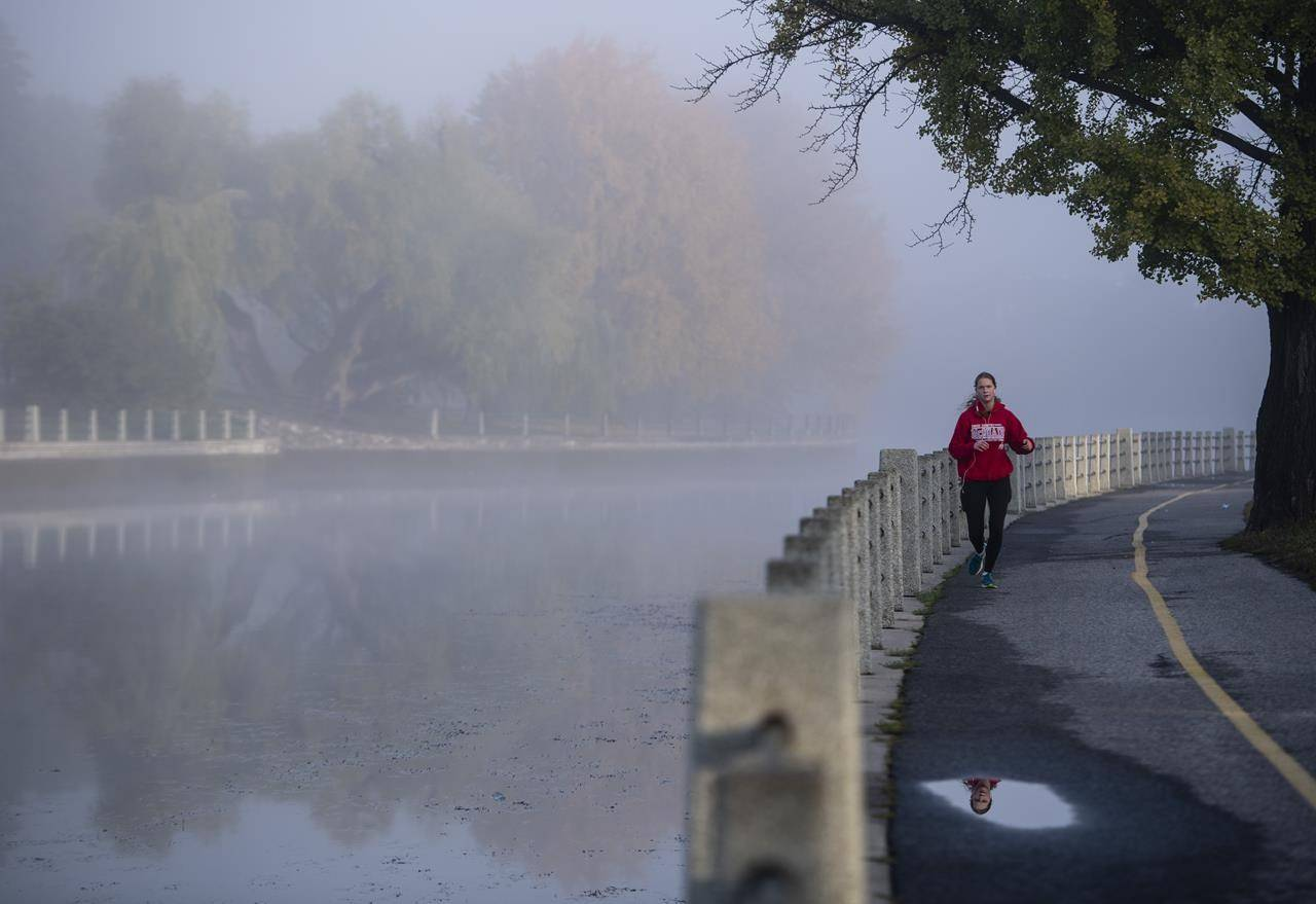 A runner makes their way along a pathway as fog blankets the Rideau Canal in Ottawa, on Wednesday, Oct. 14, 2020. New fitness guidelines urge adults to limit screen time and sedentary behaviour while finding ways to stay active, even amid the pandemic. THE CANADIAN PRESS/Justin Tang