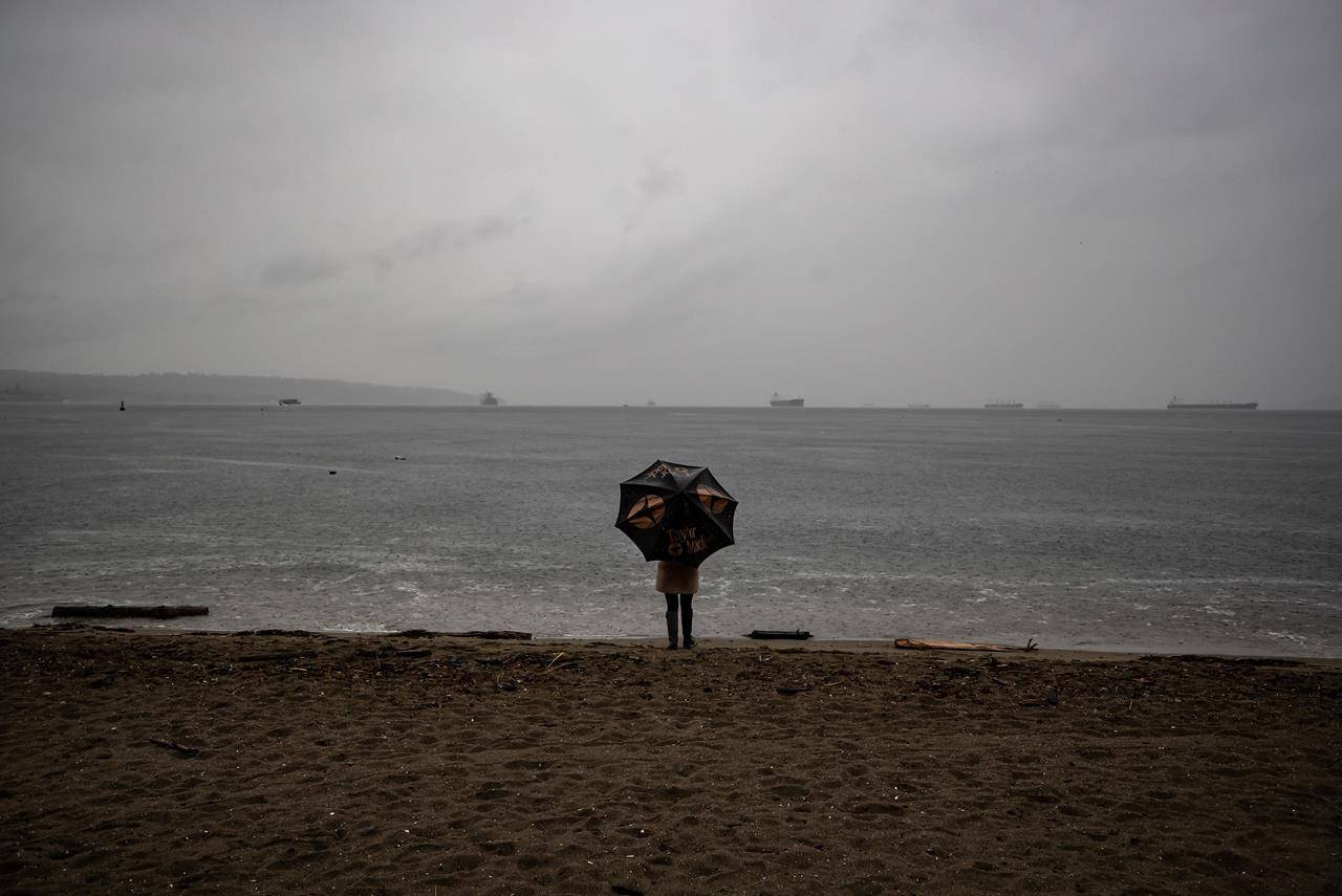 A new report on the mental health of Canadian workers suggests loneliness is worse for many people than the fear of dying from COVID-19. A person stands under an umbrella while looking out at English Bay as heavy rain falls, in Vancouver, B.C., Sunday, Oct. 11, 2020. THE CANADIAN PRESS/Darryl Dyck