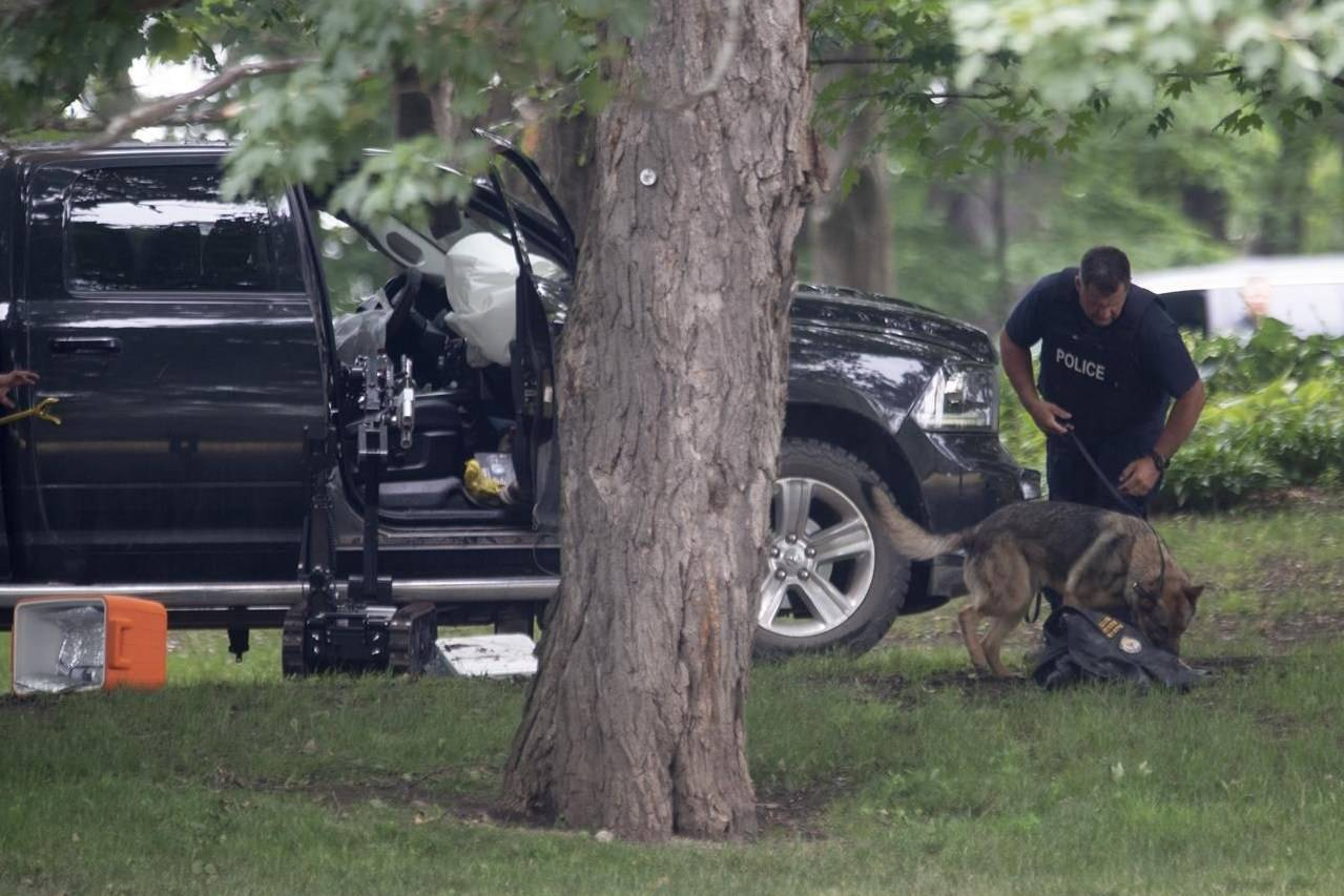An RCMP officer works with a police dog as they move through the contents of a pick up truck on the grounds of Rideau Hall in Ottawa, Thursday, July 2, 2020. THE CANADIAN PRESS/Adrian Wyld