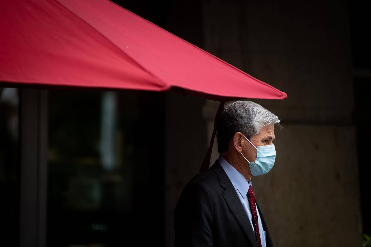 Liberal Leader Andrew Wilkinson stands under a patio umbrella during a campaign stop at a cafe, in Coquitlam, B.C., on Thursday, October 15, 2020.The B.C. Liberals announced Thursday that Laurie Throness was not representing the party in Chilliwack-Kent after making comments at an all-candidates meeting comparing free birth control to eugenics. THE CANADIAN PRESS/Darryl Dyck