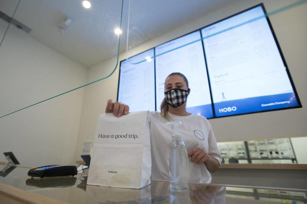 Employee Sophia Lovink shows off a bag of merchandise in Toronto on Thursday, June 11, 2020. (THE CANADIAN PRESS/Nathan Denette)