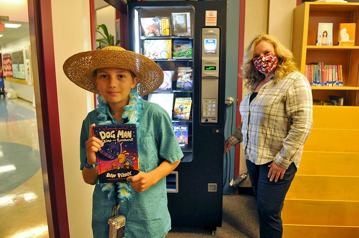 Grade 5 Unsworth elementary student Zachary Greenwood holds up the first book obtained from the school's new book vending machine as librarian, Lorraine Warner, watches on Friday, Oct. 16, 2020. (Jenna Hauck/ Chilliwack Progress)