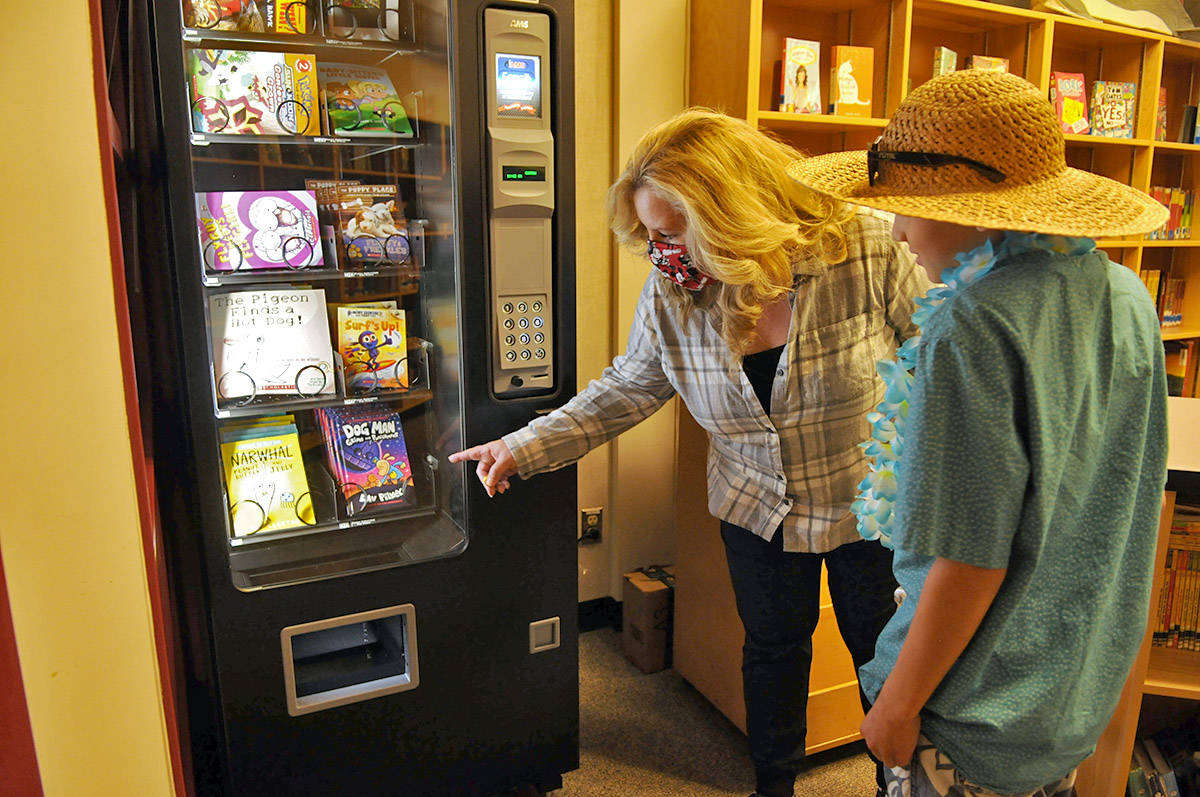 Unsworth elementary school librarian, Lorraine Warner, explains to Grade 5 student, Zachary Greenwood, how to use the new book vending machine on Friday, Oct. 16, 2020. (Jenna Hauck/ Chilliwack Progress)
