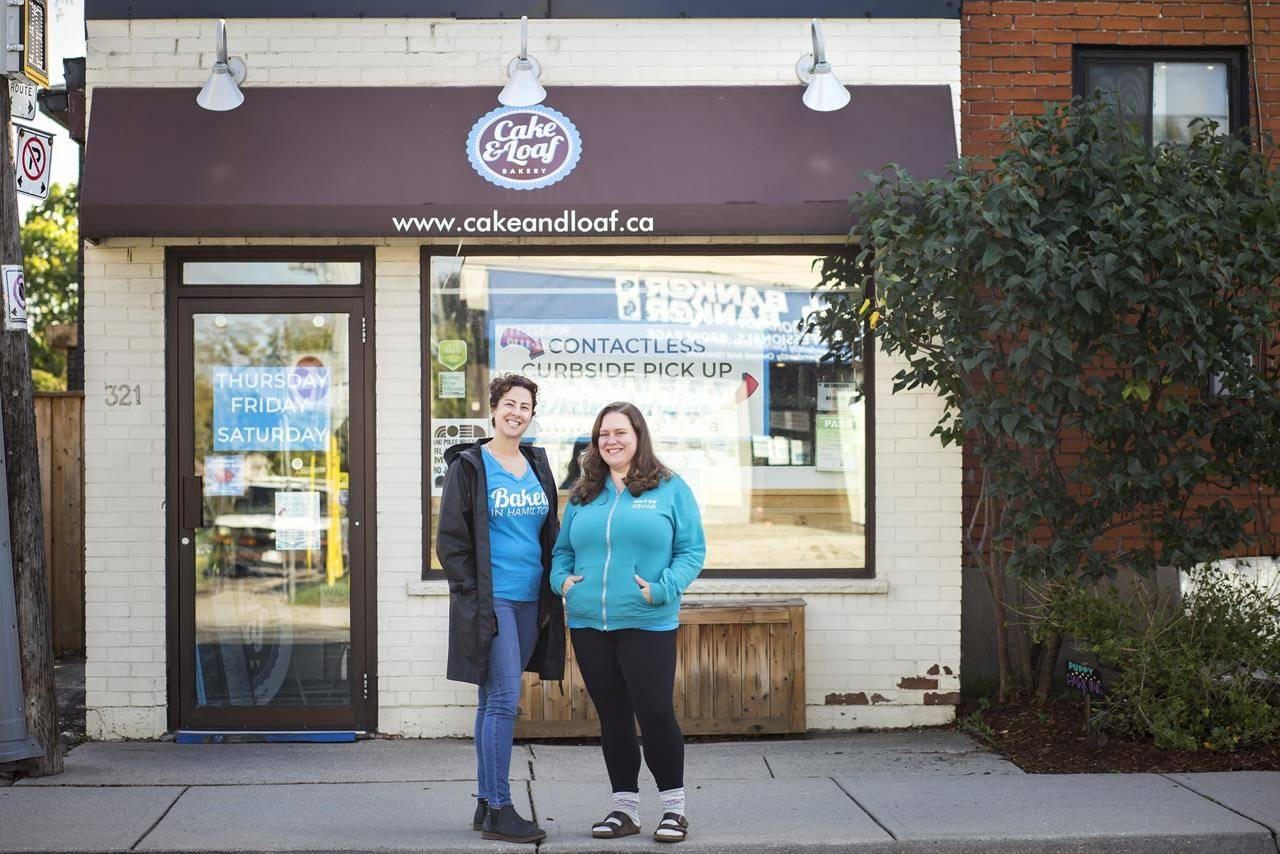 Nickey Miller, left, and Josie Rudderham, co-owners of Cake and Loaf in Hamilton, Ont., pose outside of their Dundurn Street South storefront location, Monday, October 5, 2020. THE CANADIAN PRESS/Tara Walton