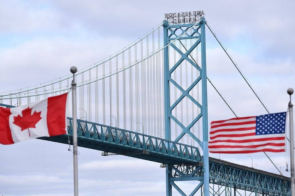 Canadian and American flags fly near the Ambassador Bridge at the Canada-USA border crossing in Windsor, Ont. on Saturday, March 21, 2020. Restrictions on non-essential travel between Canada and the United States are being extended until at least Nov. 21. THE CANADIAN PRESS/Rob Gurdebeke