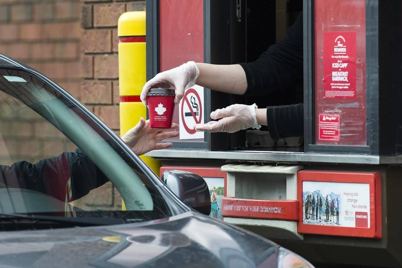 A Tim Hortons employee hands out coffee from a drive-through window to a customer in Mississauga, Ont., on March 17, 2020. Tim Hortons is ending the practice of double cupping hot drinks, a move the fast food restaurant says will eliminate hundreds of millions of cups from landfills each year. THE CANADIAN PRESS/Nathan Denette