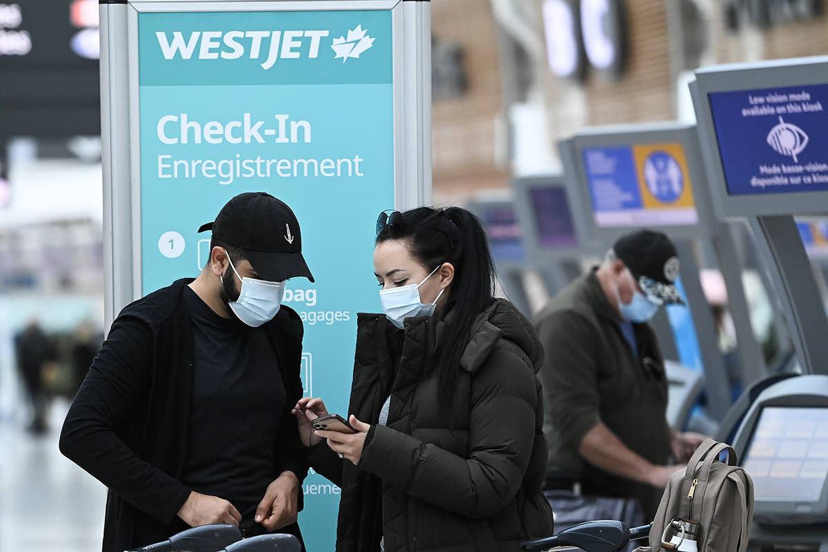 People check in at WestJet at Pearson International airport during the COVID-19 pandemic in Toronto on Wednesday, Oct. 14, 2020. Westjet has announced that it will be laying off staff and cutting flights to some cities in Atlantic Canada. THE CANADIAN PRESS/Nathan Denette