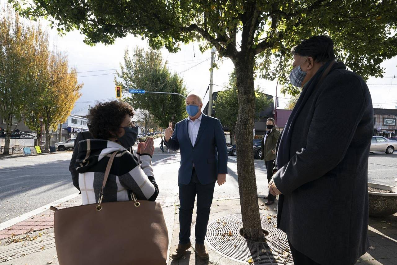 Local candidates Pam Alexis, Abbotsford-Mission, and Preet Rai, Abbotsford-West, look on as NDP Leader John Horgan main streets in Abbotsford, B.C., Wednesday, October 21, 2020. THE CANADIAN PRESS/Jonathan Hayward