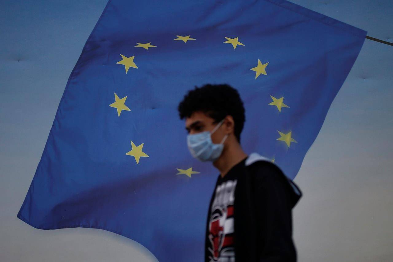 Backdropped by a poster with a European Union flag, a youth wearing a mask to help protect against the spread of coronavirus walks in Istanbul, Friday, Oct. 2, 2020. The European Union's council has re-imposed a travel restriction on Canada as it battles a second wave of the COVID-19 pandemic. THE CANADIAN PRESS/AP/Emrah Gurel
