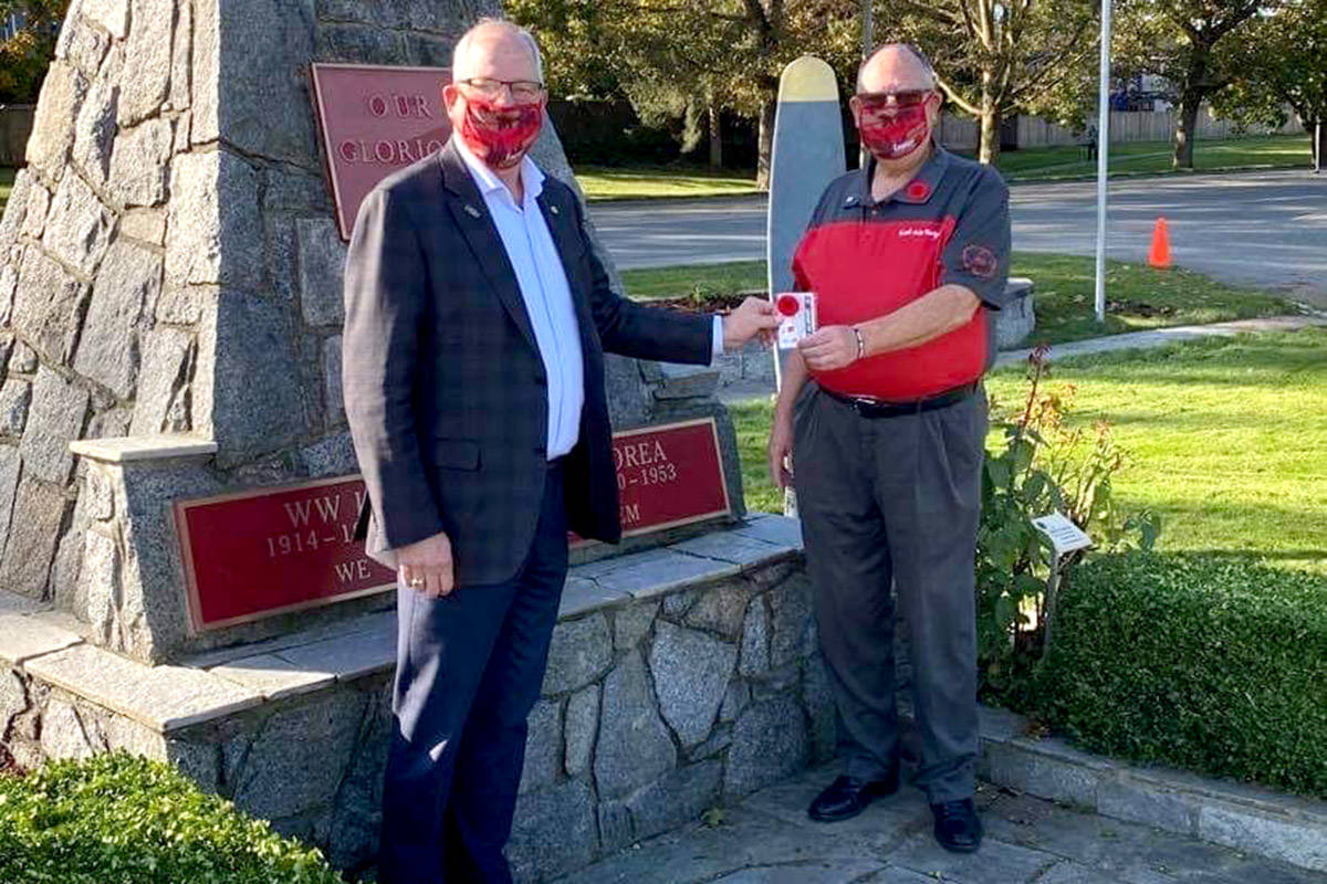 Aldergrove legion Branch 265 president Doug Hadley presents a poppy to Langley Township mayor Jack Froese. (Madeline Roach/Special to the Aldergrove Star)