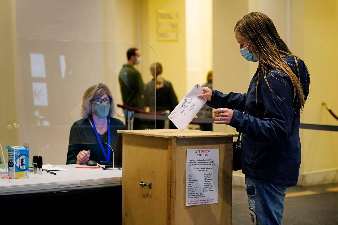 A voter places her absentee ballot in the ballot box, Wednesday, Oct. 7, 2020, at Merrill Auditorium in Portland, Maine. THE CANADIAN PRESS/AP/Robert F. Bukaty