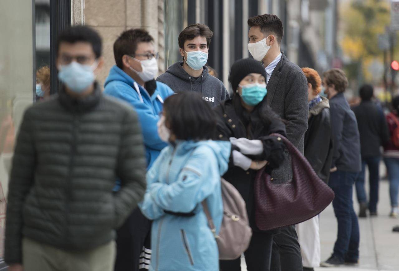 People wear face masks as they wait to enter a store in Montreal on October 24, 2020, as the COVID-19 pandemic continues in Canada and around the world. THE CANADIAN PRESS/Graham Hughes