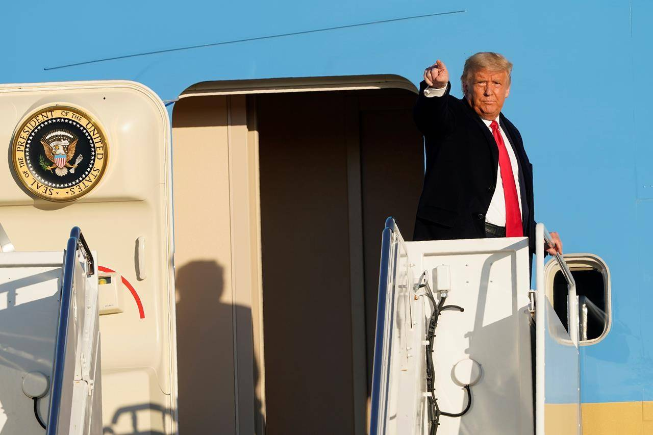 President Donald Trump gestures from the top of the steps of Air Force 1 at Andrews Air Force Base, Md., Wednesday, Oct. 21, 2020. When people in the United States talk about moving to Canada to escape four more years of Donald Trump, it's usually either a punchline or a pipe dream. THE CANADIAN PRESS/AP-Susan Walsh