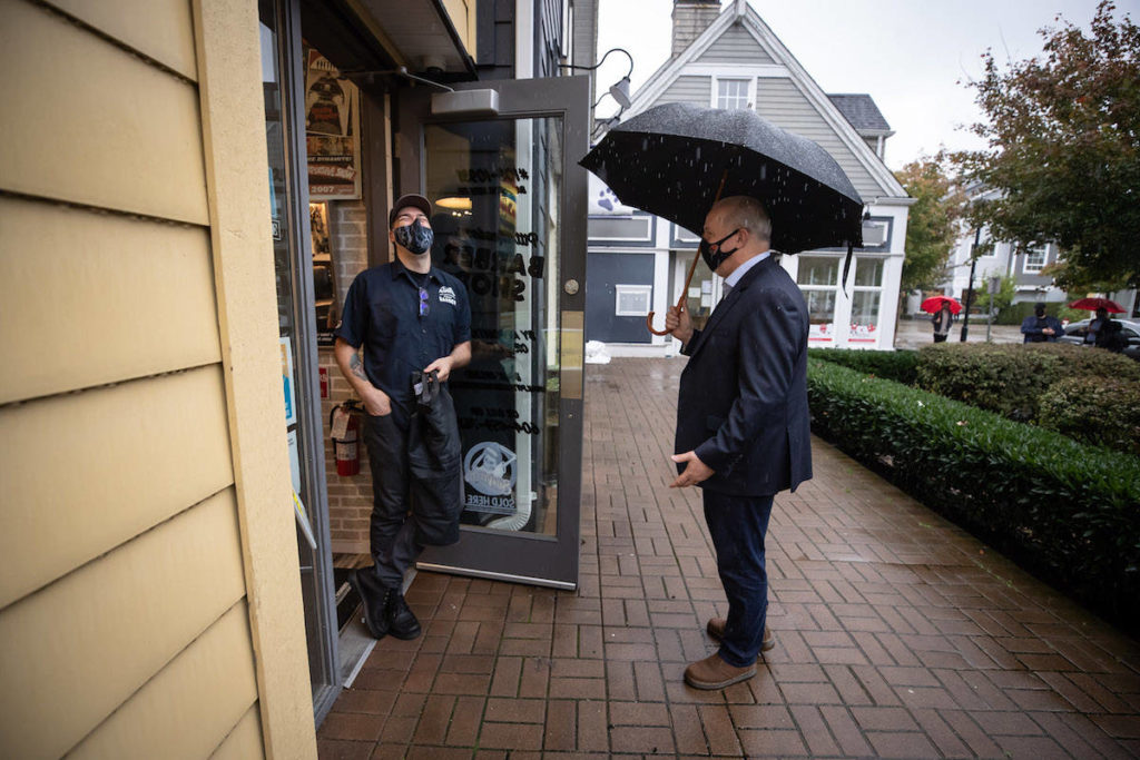 NDP Leader John Horgan speaks with the owner of a barber shop while campaigning in Pitt Meadows, B.C., on Friday, Oct. 16, 2020. Campaigning was restricted by the coronavirus pandemic. THE CANADIAN PRESS/Darryl Dyck