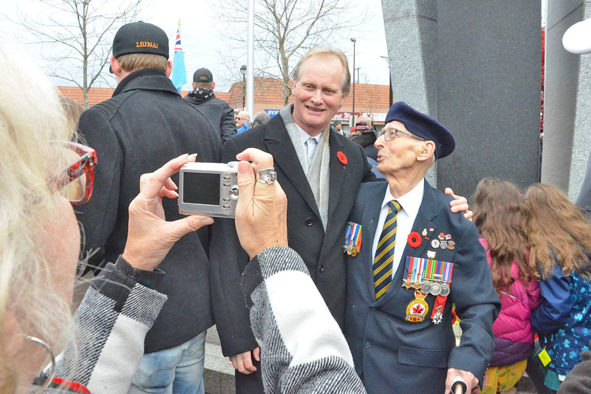 A veteran posed for a picture by the Langley City cenotaph at the 2019 Remembrance Day service. This year, because of the pandemic, organizers are moving the event online, with a few extras. (Langley Advance Times file)