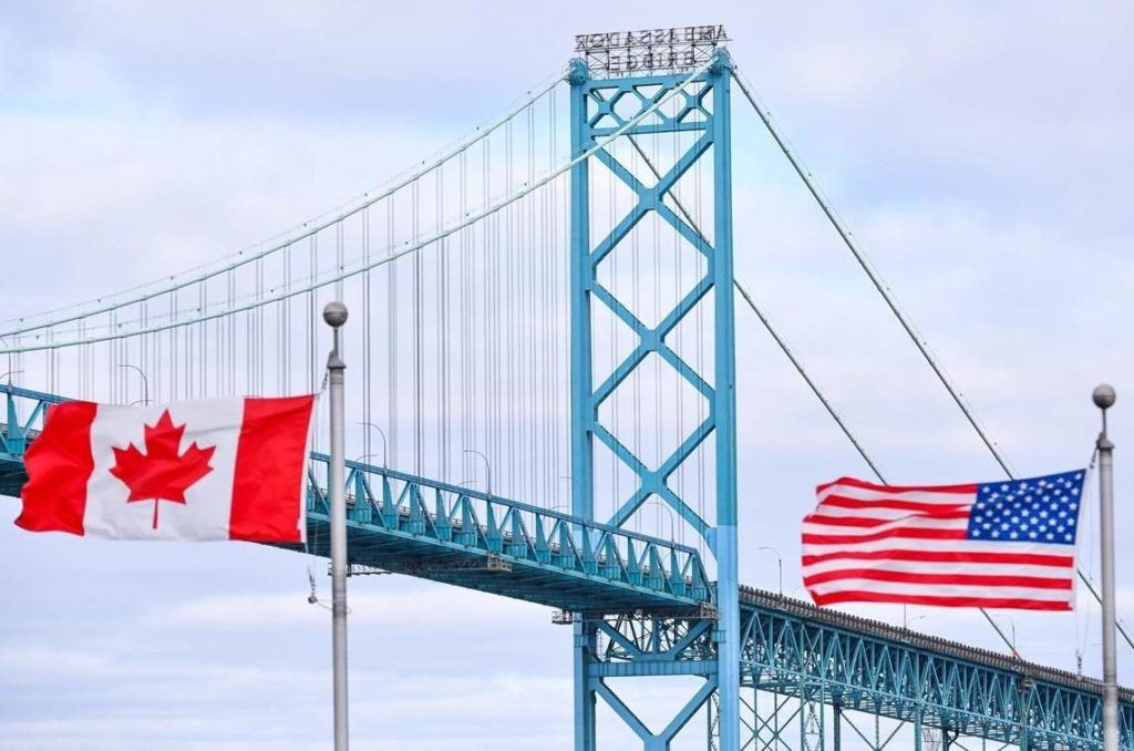 Canadian and American flags fly near the Ambassador Bridge at the Canada/USA border crossing in Windsor, Ont. on Saturday, March 21, 2020. THE CANADIAN PRESS/Rob Gurdebeke