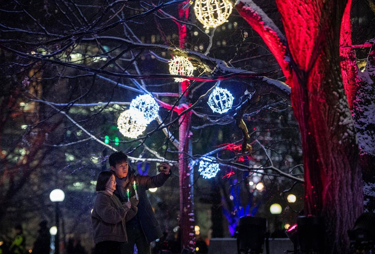 People take a photo together during the opening night of Christmas Lights Across Canada, in Ottawa, on Wednesday, Dec. 4, 2019. The likelihood that most Canadians will enjoy a holly jolly Christmas season of gatherings, caroling and travel is unlikely, say public health experts who encourage those who revel in holiday traditions to accept more sacrifices ahead. THE CANADIAN PRESS/Justin Tang