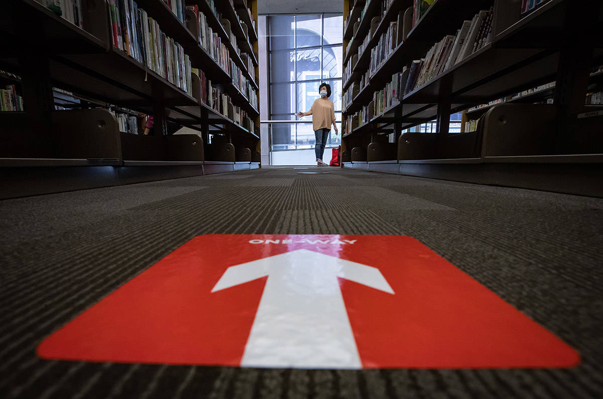 A woman wears a face mask and plastic gloves while browsing books as a sticker on the floor indicates a one-way direction of travel between shelves of books at the Vancouver Public Library's central branch, after it and four other branches reopened with limited services, in Vancouver, on Tuesday, July 14, 2020. (THE CANADIAN PRESS/Darryl Dyck)