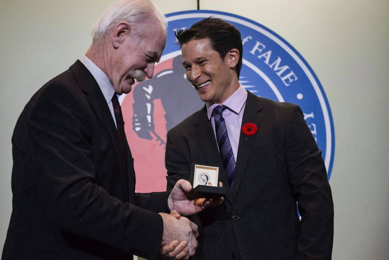 Lanny McDonald, chair of the Hockey Hall of Fame, left, awards 2017 inductee Paul Kariya with a ring during a press conference in Toronto, on Friday, November 10, 2017. The Hockey Hall of Fame announced Friday there will be no new inductees in 2021, and the class of 2020 will be honoured in a ceremony that year instead. THE CANADIAN PRESS/Christopher Katsarov
