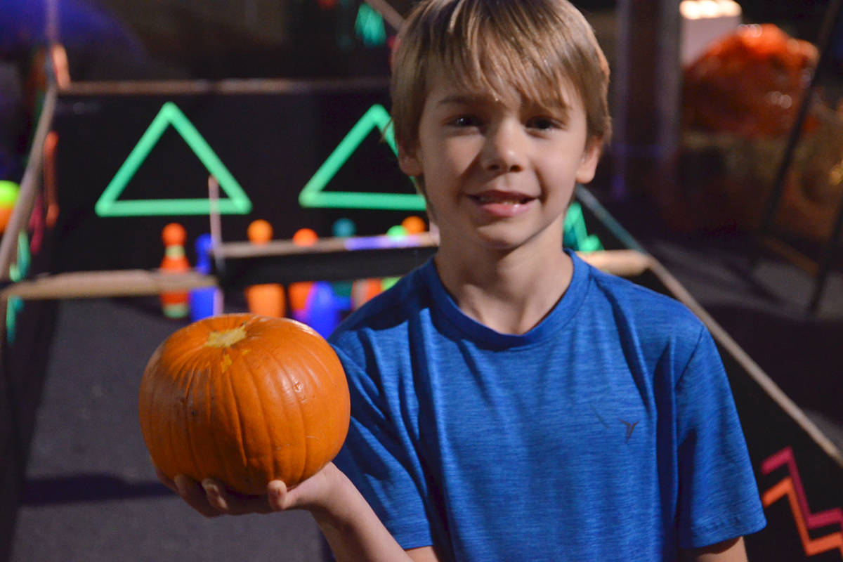 Under special lights, youngsters such as Lucas, bowled pumpkins to knock over glow in the dark bowling pins at the South Ridge Church Pumpkin Fest. (Heather Colpitts/Langley Advance Times)