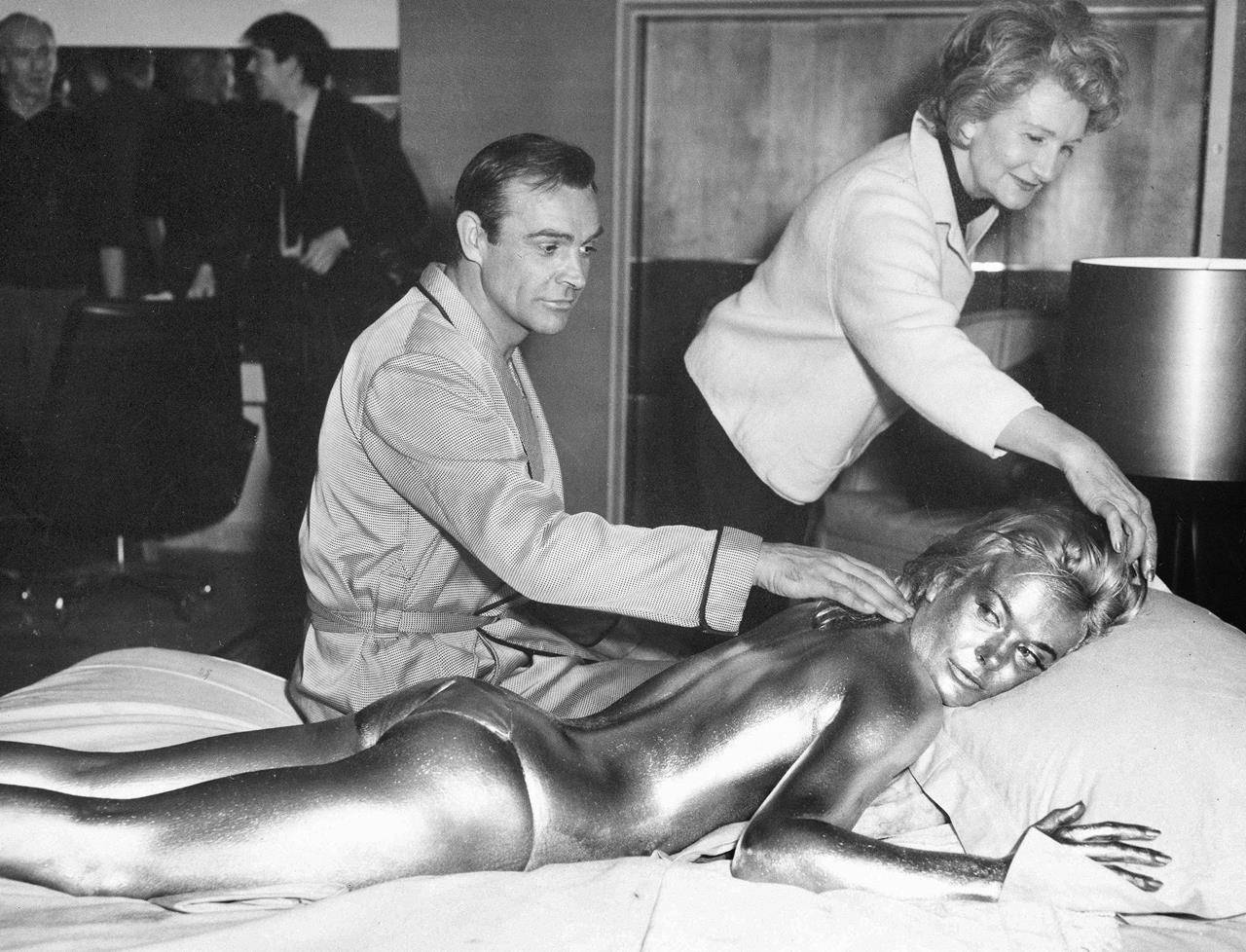 """FILE - In this file photo dated April 20, 1964, James Bond, alias, Sean Connery, finds himself in a sticky situation with actress Shirley Eaton at Pinewood Studios, near London. Miss Eaton was given a liberal coating of gold paint for a scene in the latest Bond thriller """"Goldfinger,"""" with unidentified woman at top. Scottish actor Sean Connery, considered by many to have been the best James Bond, has died aged 90, according to an announcement from his family. (AP Photo/Victor Boynton)"""