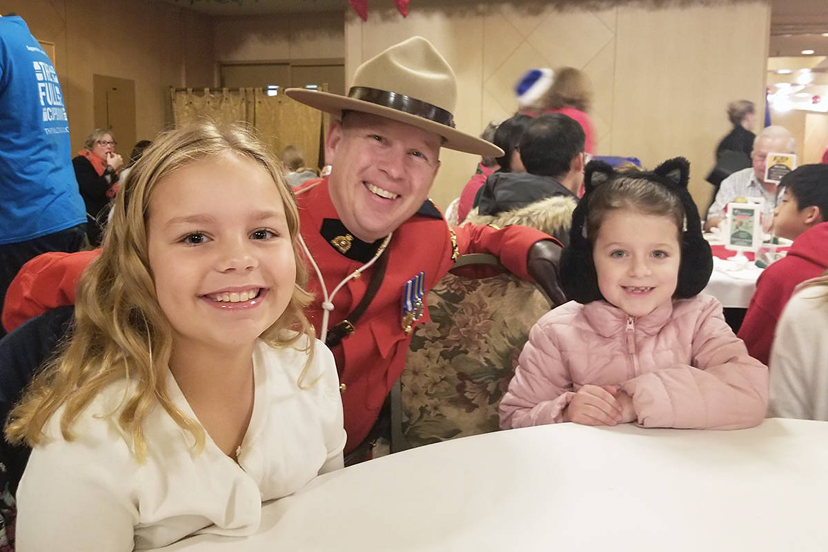 Langley RCMP Cpl. Craig van Herk and two young friends got up early to attend last year's third annual Christmas Wish Breakfast toy drive and fundraiser at Newlands Golf & Country Club. This year, due to the pandemic, the breakfast has been cancelled, instead the Langley Christmas Bureau is accepting gift cards or donations online or in-person at Langley City Hall. (Langley Advance Times file)