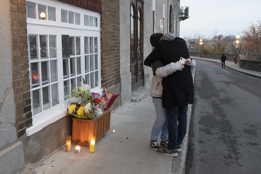 Dimitry Montigny embraces Jessica Peloquin, left, after laying flowers in front of Suzanne Clermont's house in Quebec City, Sunday, Nov. 1, 2020. Clermont was named as one of two people killed Saturday night by a man wielding a sword. Peloquin, who took the 911 call, was in tears. THE CANADIAN PRESS/Jacques Boissinot