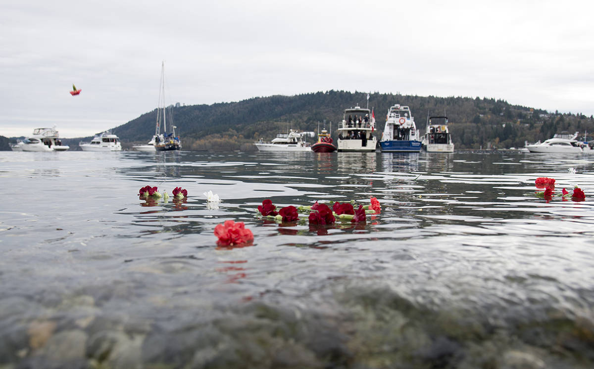 Flowers are seen floating in the sea during a maritime Remembrance Day ceremony in Burrard Inlet in North Vancouver, B.C., Monday, November, 11, 2019. THE CANADIAN PRESS/Jonathan Hayward