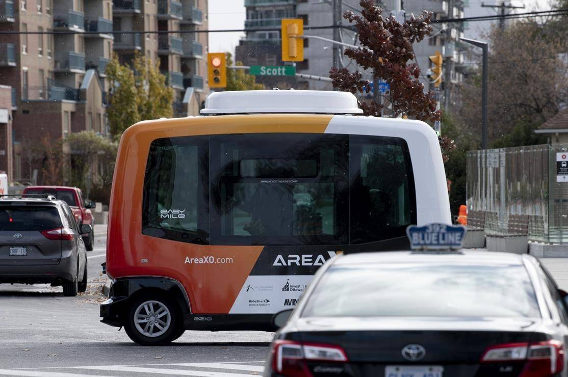 "A low-speed autonomous shuttle rides past a taxi during a demonstration on roads around government buildings in Ottawa, Monday, Nov. 2, 2020. Statistics Canada says domestic firms that invested in robots over since the late 1990s have actually expanded their workforce, suggesting a less than ""apocalyptic"" result for workers overall. THE CANADIAN PRESS/Adrian Wyld"