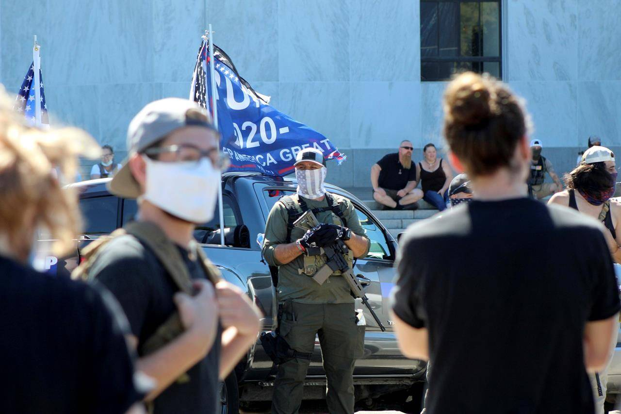 A right-wing protester armed with an AR-15 style rifle looks at Black Lives Matter counter-protesters who are across the street in front of the Oregon State Capitol in Salem, Ore., on Monday, Sept. 7, 2020. Canadians are watching in fear today as their American neighbours vote in earnest, capping a campaign marked by rising voter intimidation, threats of postelection violence, and the potential breakdown of democracy itself. THE CANADIAN PRESS/AP-Andrew Selsky