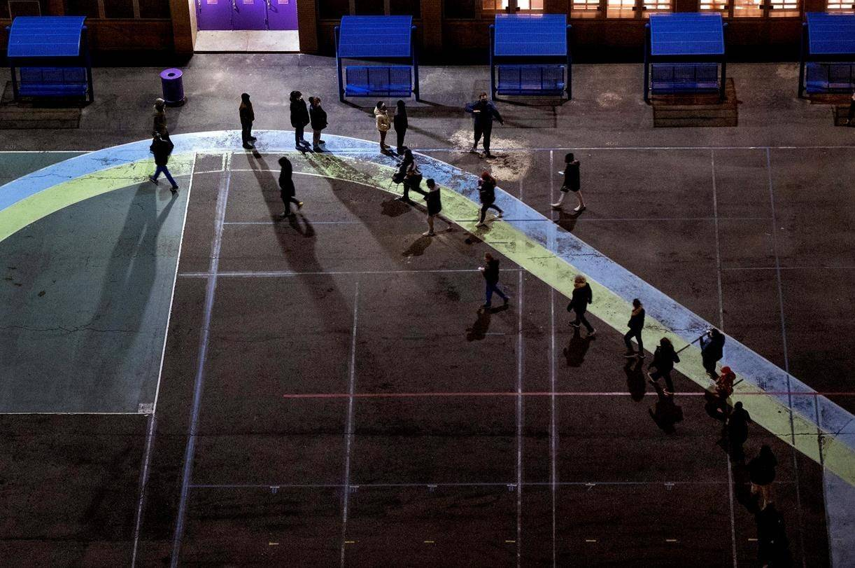 People line up on a playground before the door of a polling place opened at an elementary school in the Manhattan borough in New York Tuesday, Nov. 3, 2020. (AP Photo/Craig Ruttle)