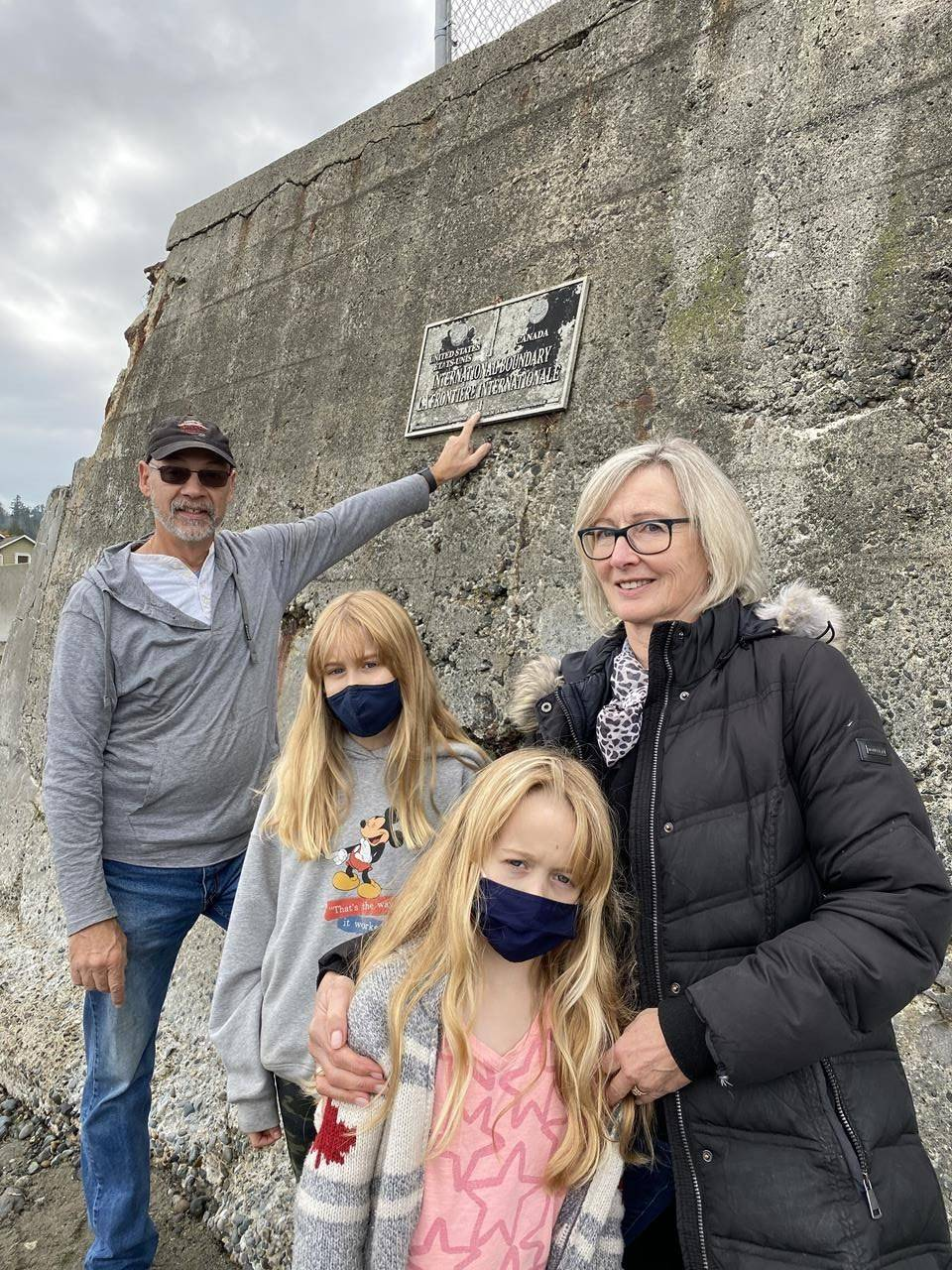 Steve Power points to a plaque noting the international boundary between Canada and the United States as he stands on the American side of a beach in Point Roberts and his wife, Patsy Reis-Power visits him with their granddaughters on the Canadian side at Centennial Beach in Delta, B.C. Power took a plane to Point Roberts, where the couple owns property, because he couldn't cross the land border due to COVID-19 restrictions that both Americans and Canadians want eased during the pandemic. THE CANADIAN PRESS/Camille Bains