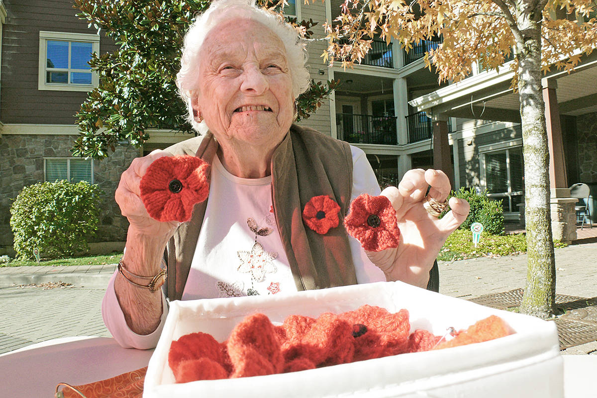 Irene Brummitt was waiting with her hand-knitted Remembrance Day poppies for donors to arrive at the entrance to the Avalon seniors residence in Murrayville on Sunday, Nov. 1, 2020. It was her third year making poppies to help with the annual veterans fundraiser. (Dan Ferguson/Langley Advance Times)