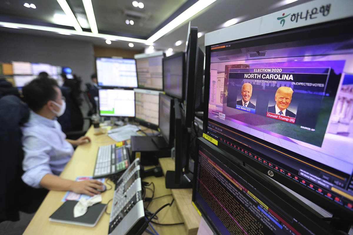 A screen shows a live broadcasting of a news program on the U.S. elections as a currency trader works at the foreign exchange dealing room of the KEB Hana Bank headquarters in Seoul, South Korea, Wednesday, Nov. 4, 2020. (AP Photo/Ahn Young-joon)