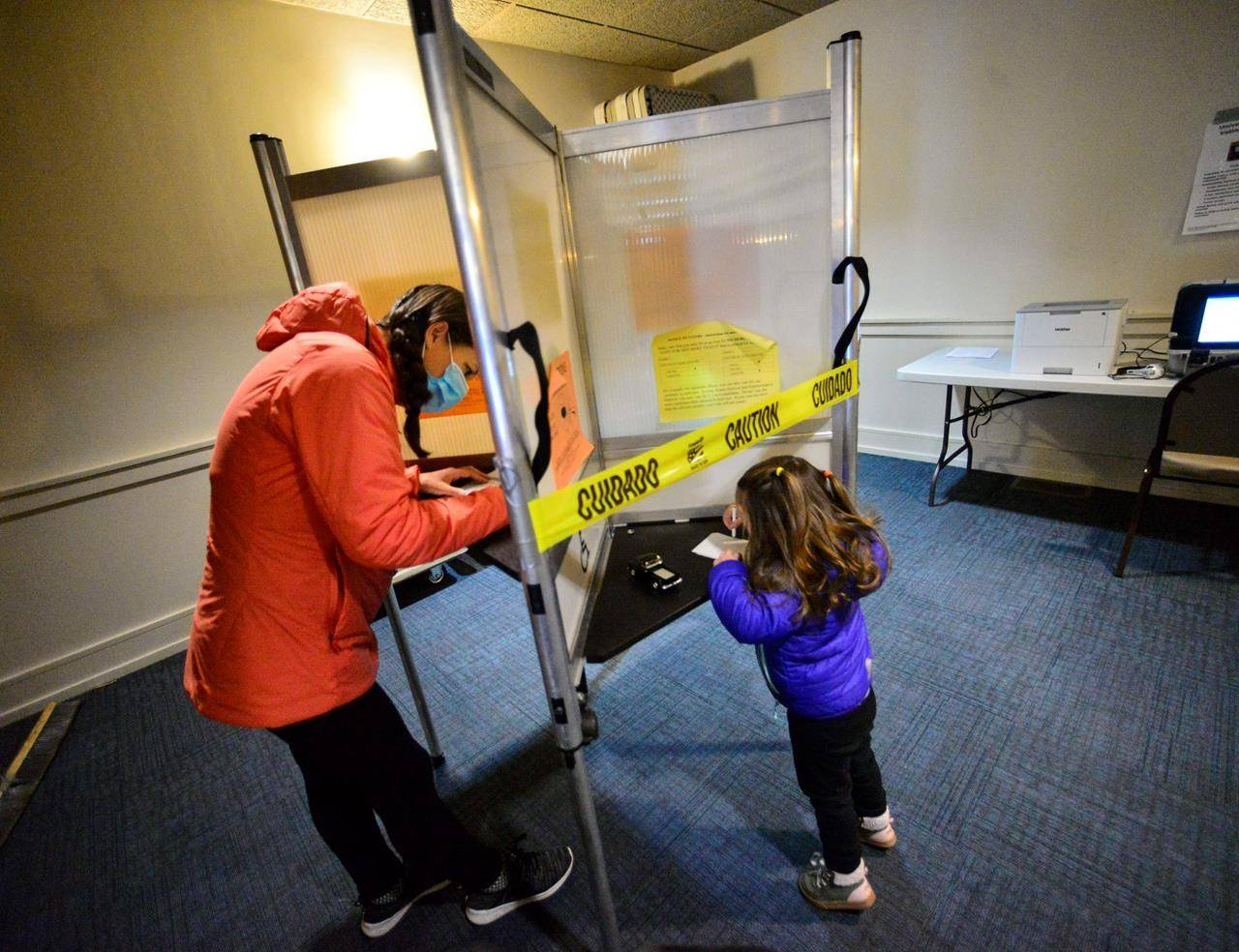 Tricia Suriani, of Brattleboro, Vt., fills out her ballot while her 2-year-old daughter, Clemencia, draws a picture inside a voting booth during Election Day, on Tuesday, Nov. 3, 2020 in Brattleboro, Vt. (Kristopher Radder /The Brattleboro Reformer via AP)