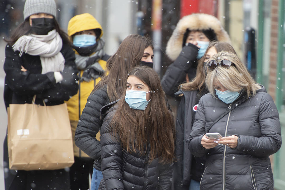 Pedestrians protect themselves from the cold and COVID-19 as they wait for a light to change, Tuesday, November 3, 2020 in Montreal.THE CANADIAN PRESS/Ryan Remiorz
