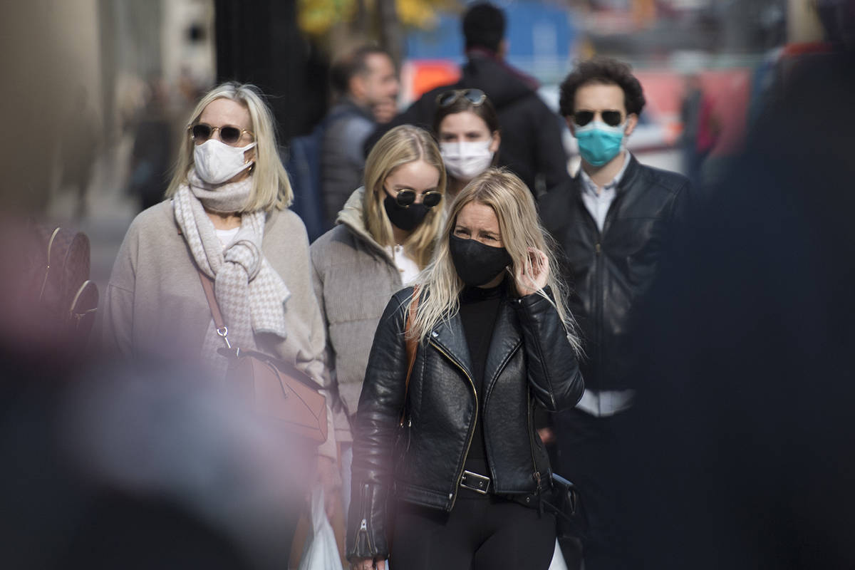 People wear face masks as they walk along a street in Montreal, Sunday, Oct. 18, 2020, as the COVID-19 pandemic continues in Canada and around the world. THE CANADIAN PRESS/Graham Hughes