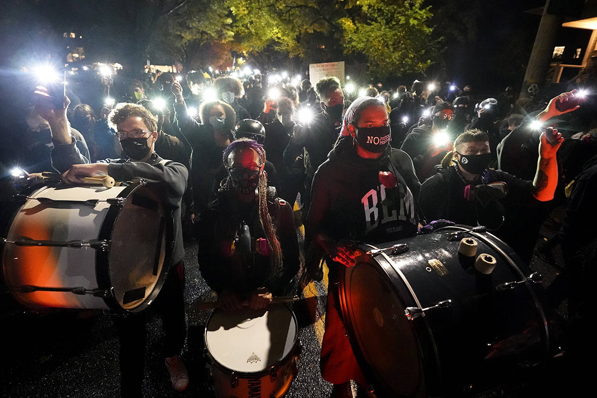 People use the lights on their phones as they march on the night of the election, Tuesday, Nov. 3, 2020, in Portland, Ore. (AP Photo/Marcio Jose Sanchez)