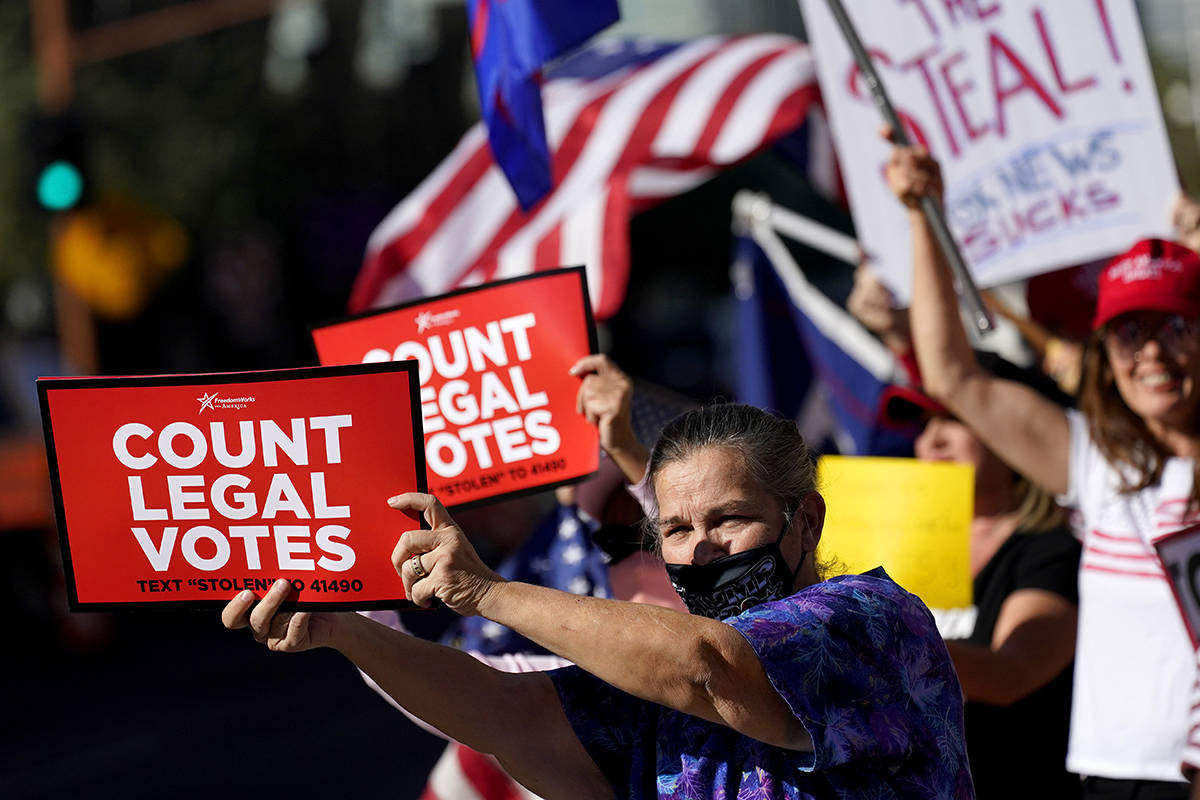 People rally outside City Hall, Thursday, Nov. 5, 2020, in Phoenix. Dozens of pro-Trump protesters gathered to protest after Democratic challenger Joe Biden was reported to have flipped the Republican stronghold of Arizona. (AP Photo/Matt York)