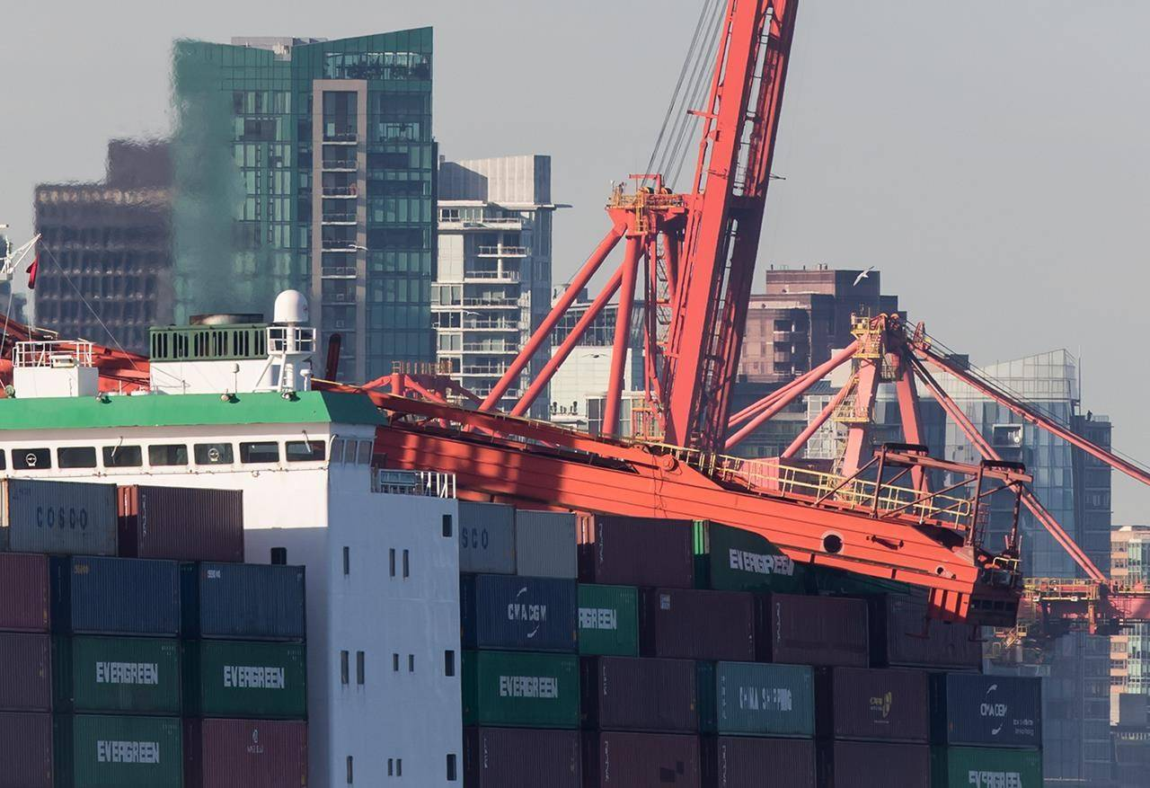 A large crane that collapsed rests on top of cargo containers on a freighter at Port Metro Vancouver's Vanterm facility, in Vancouver on January 28, 2019. The Transportation Safety Board says the Port of Vancouver may be close to exceeding its ability to safely handle large-sized container ships. The board makes the comment in its report into a January 2019 incident where the container vessel Ever Summit hit a crane while being piloted into its berth at the Vanterm terminal in the Port of Vancouver. THE CANADIAN PRESS/Darryl Dyck