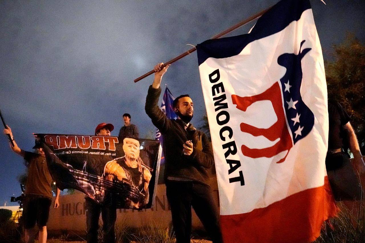 A supporter of Democrat Joe Biden waves a flag near supporters of President Trump in front of the Clark County Election Department, Thursday, Nov. 5, 2020, in Las Vegas. (AP Photo/Jae C. Hong)