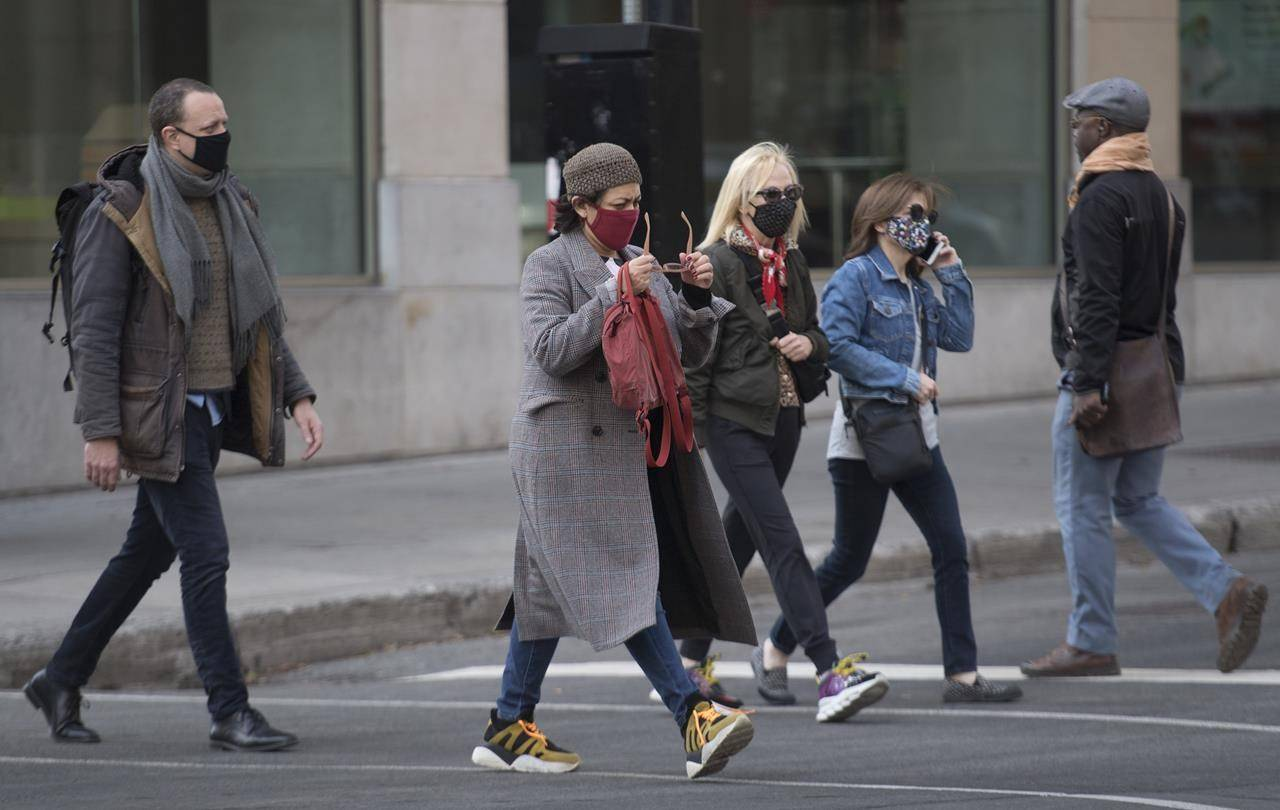 People wear face masks as they walk along a street in Montreal, Saturday, November 7, 2020, as the COVID-19 pandemic continues in Canada and around the world. THE CANADIAN PRESS/Graham Hughes