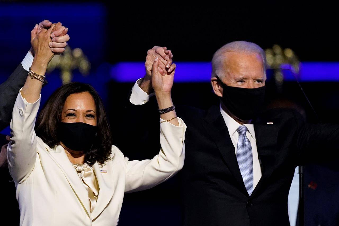 Vice President-elect Kamala Harris holds hands with President-elect Joe Biden and her husband Doug Emhoff as they celebrate, in Wilmington, Del., Saturday, Nov. 7, 2020. Federal cabinet ministers are welcoming Joe Biden election as the next U.S. president as an opportunity to advance the fight against climate change. THE CANADIAN PRESS/AP-Andrew Harnik
